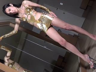Shiny gold suit and gloves on a hard rod Oriental ladyboy